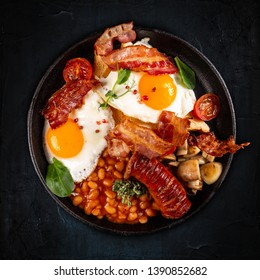 Flat lay of Full English Breakfast including sausages, grilled tomatoes and mushrooms, egg, bacon and baked beans