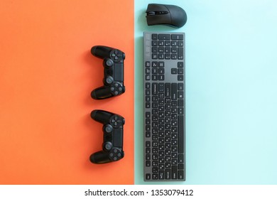 Flat lay of game set or kit with two arcade joystick, black computer mouse and modern keyboard lying isolated against colorful background
