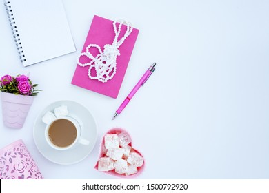 Flat lay girly, pale pink items for planning, notepads, pens, office work or working at home on her laptop, on the pale white background, with place for labels. Concept Desk.