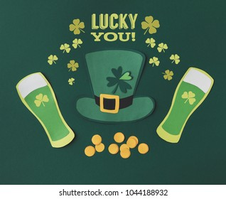 flat lay with glasses of beer, coins, green hat, shamrocks and lucky you lettering on green background