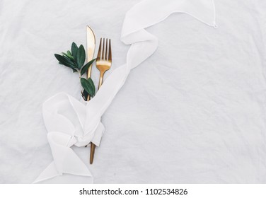 Flat lay gold cutlery with olive branch. Top view, copy space
