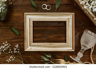 Flat lay gold frame with wedding decorations on wooden background