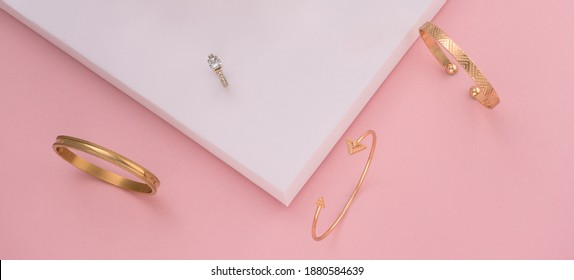 Flat lay of golden bracelets and ring on pink and white papers