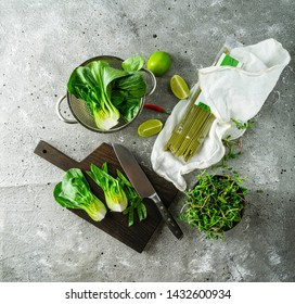 Flat lay of green colored ingredients for cooking an Asian meal: baby bok choy, green sprouts, green tea dry noodles, and lime on a gray background.