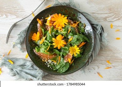 flat lay of green plate with arugula, orange, sesame seeds and edible marigold flowers salad on light table, vegetarian food concept