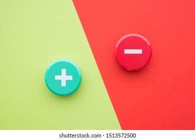 Flat lay of green plus and red minus symbol plastic botton on green and red background with copy space. Concept of difference, opposites plus vs minus or pros vs cons.