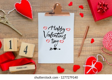 Flat lay greeting card. Clipboard with text Happy Valentine's Day, red hearts, rope, ribbon, perpetual calendar with date 14 february, gift box, pen on wooden background. Saint Valetine day decoration