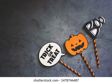 Flat lay of halloween prop for photo booth and party on dark stone background with copy space, holiday concept