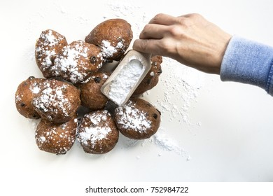 flat lay, hand sprinkling sugar on traditional oliebollen, oil dumpling or fritter, with wooden spoon, for Dutch New Year's Eve