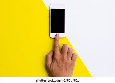 Flat lay hand using phone blank screen on top view,background in pastel colors.clipping path inside