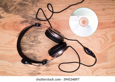 Flat lay - headphones and compact disc on wooden desk