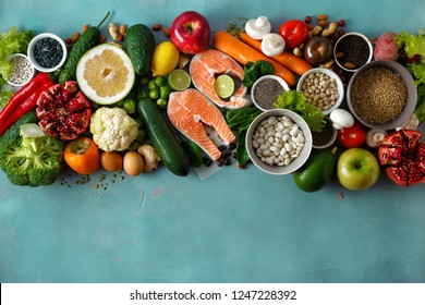 Flat lay healthy and diet food (cereals, seeds, fish, vegetables and fruits) on stone background top view