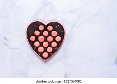 Flat lay. Heart chape box with pink chocolates.