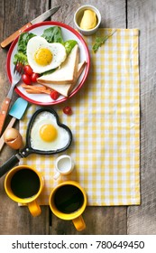 Flat lay heart shape sunny side up breakfast on rustic wooden background.
