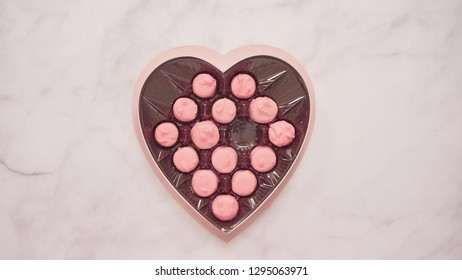 Flat lay. Heart shaped box of pink chocolated for Valentine's Day.