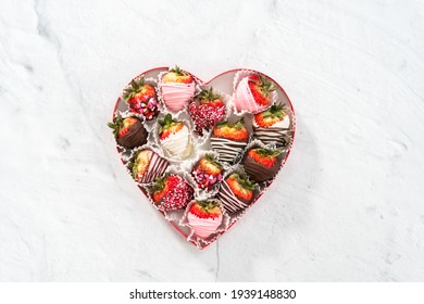 Flat lay. Heart shaped box with assorted chocolate covered strawberries on a white background.
