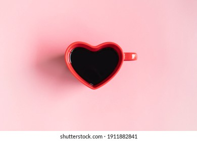 Flat lay of heart shaped cup of black coffee on a pink background with copy space. top view. Valentine's day, beverage concept