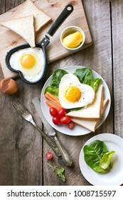 Flat lay heart shaped sunny side up breakfast with coffee on rustic wooden table top.