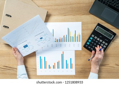Flat lay high angle above top view cropped lady in her formalwear shirt she sit behind desktop table in workplace loft interior calculate trade on diagram hold blank in hands