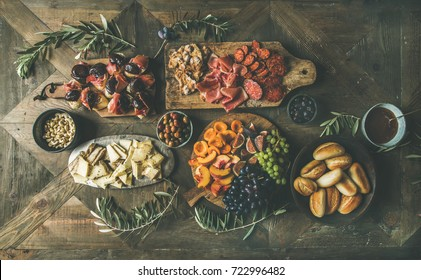 Flat lay of holiday, party, family dinner table set with wine snacks. Meat, cheese, olives, crostini sandwiches, prosciutto, bread over wooden background, top view. Finger food, catering food concept