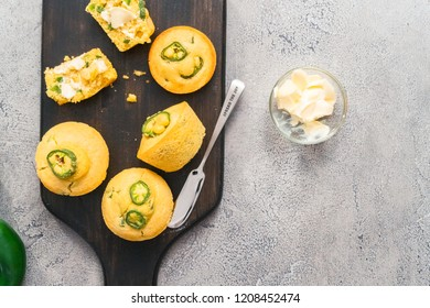 Flat lay. Home made cornbread muffins with spicy jalapeno pepper with spread of butter.