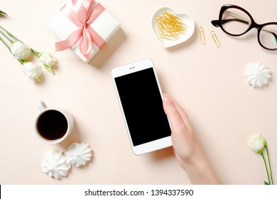Flat lay home office desk. Female workspace with human hand holding smartphone, coffee cup, glasses, flowers, golden accessories on pink background. Top view feminine background.