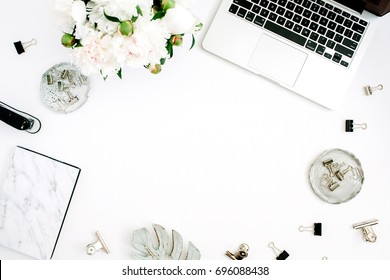 Flat lay home office desk frame with space for text. Female workspace with laptop, white peony flowers bouquet, accessories, marble diary on white background. Top view feminine background.