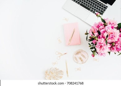 Flat lay home office desk. Woman workspace with laptop, pink peonies bouquet. Top view feminine background.