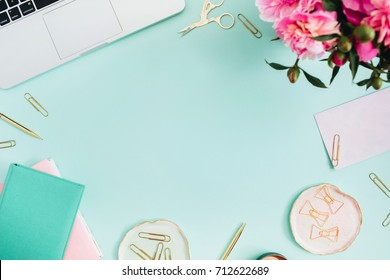 Flat lay home office desk. Female workspace with laptop, pink peonies bouquet, golden accessories, pink and mint diary on mint background. Top view feminine background.
