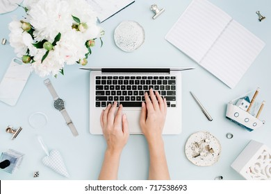 Flat lay home office desk. Women workspace with female hands, laptop, white peony flowers bouquet, accessories on blue background. Top view feminine background. Girl working on laptop.