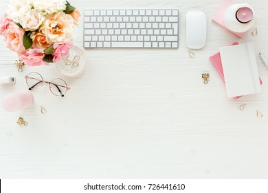 Flat lay home office desk. Female workspace with computer, pink and beige roses flowers bouquet, accessories, diary, glasses on white wooden background. Top view feminine background.