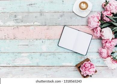 Flat lay home office desk.Pink peony bouquet, coffee and notebook on wooden background.Top view feminine. Flat lay home office desk. Woman workspace