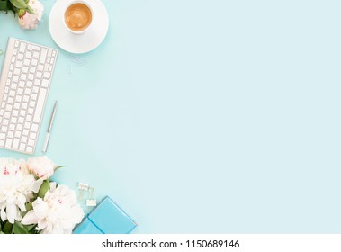 Flat lay home office workspace background with white modern keyboard, notebook and peony flowers, copy space on blue background banner