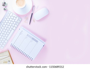 Flat lay home office workspace - white modern keyboard with notebook on pink background