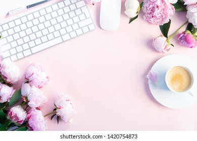 Flat lay home office workspace - modern keyboard with female accessories and fresh peony flowers, copy space on pink background