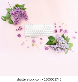 Flat lay home office workspace - modern keyboard with lilac flowers over pink desk