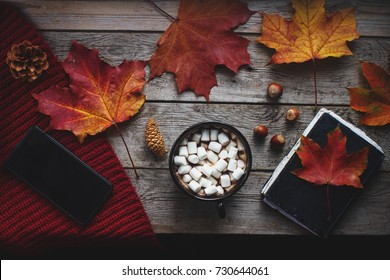 Flat lay of homemade cocoa with marshmallows, autumn leaves, notebook and smartphone on rustic wooden table, cozy autumn still life, autumn mood concept, blogger lifestyle, top view, selective focus
