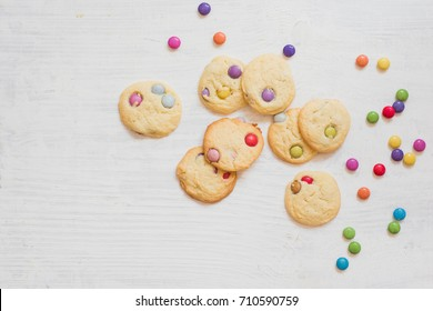 Flat lay with homemade sugar cookies with colorful chocolate candies for fun kids birthday party celebrations on white wooden background with space for copy text or message