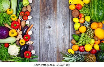 Flat lay of huge group of fresh vegetables and fruit on wooden background - Vegetables VS Fruit - High quality studio shot -  Flat lay