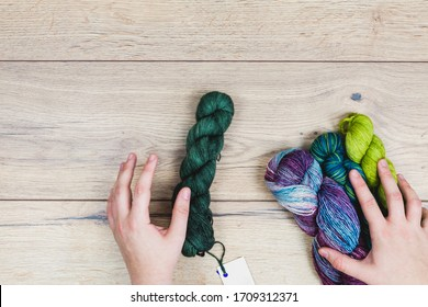 Flat lay of human hands choosing beautiful skeins in purple and green tones with blank label for mock up over a wooden table