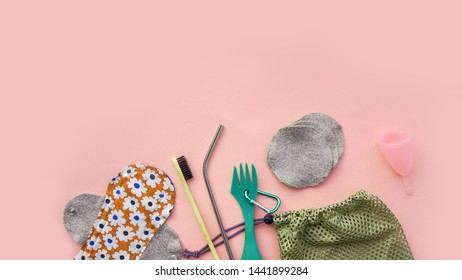 Flat lay of hygiene and care items arranged on pink surface, zero waste concept
