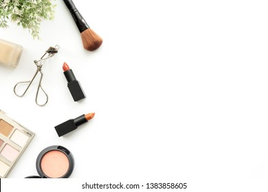 Flat lay image of beauty cosmetics make up with lipsticks, eye shadow palette, blush on, concealer, foundation and brushes. Top view with copy space, for your text.
