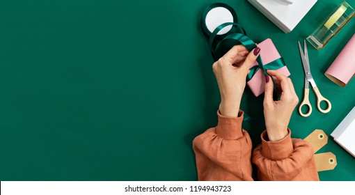 flat lay image of female hands package gifts on pink background. holidays concept, copy space