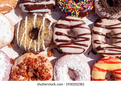 flat lay image of fresh made store bought donuts in paper box fresh out of the donut shop. An assortment with different flavors and toppings are packed together on flat box, a sweet summer treat