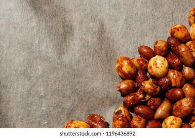 Flat lay image of raw spiced peanuts ready to be roasted on brown baking paper with room for text.