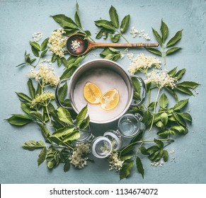 Flat lay of ingredients for seasonal traditional making of syrup and elderberry flowers: cooking pot, wooden spoon, sugar, lemon and glass jars on blue kitchen table background, top view