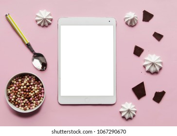Flat lay. Ipad Mock up. Top view.  Sweet tooth table. Chokolate, spoon and creaspy with ipad on the pink background. Food blog concept.
