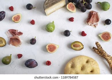 Flat lay italian aperitivo Wine appetizer Fig Prosciutto Grape Plum Cheese Focaccia Grissini Raspberry White background Copy space