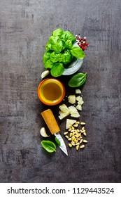 Flat lay of italian pesto sauce organic ingredients on dark vintage background. Top view, copy space.