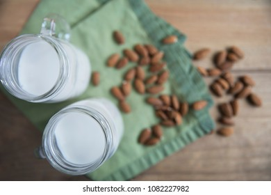 Flat lay of jars of almond milk with raw almonds out of focus on table.